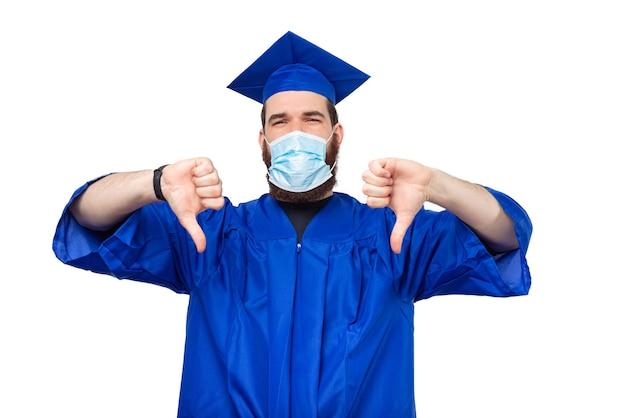 卒業した帽子と学士号を身に着けて嫌悪感を示している学生男性の写真
