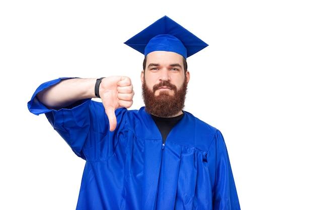 파란색 가운을 입고 싫어하는 수염을 가진 학생 남자의 사진, 아래로 엄지 손가락