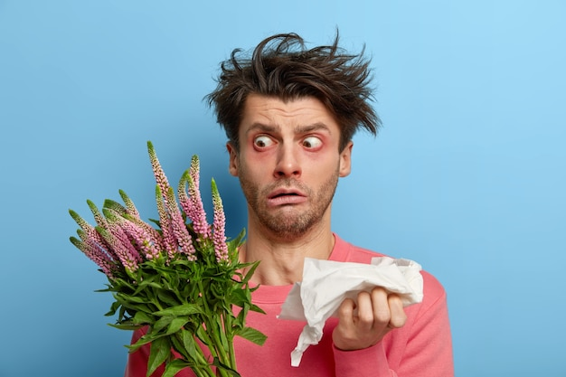 Фотография ошеломленного человека смотрит на растение широко открытыми глазами, у него растрепанные волосы, он держит салфетку, постоянно чихает, аллергическая реакция на пыльцу и цветение, чувствует себя больным и измученным из-за болезни