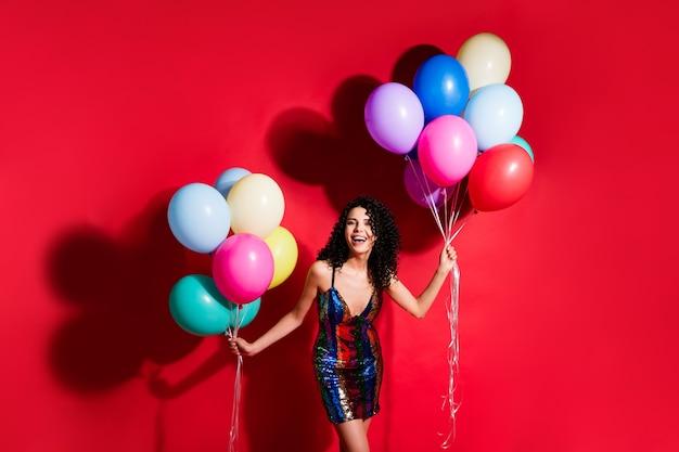 Фотография потрясающей девушки держит много воздушных шаров с открытым ртом, одетая в глянцевое мини-платье, изолированное ярким красным цветом фона