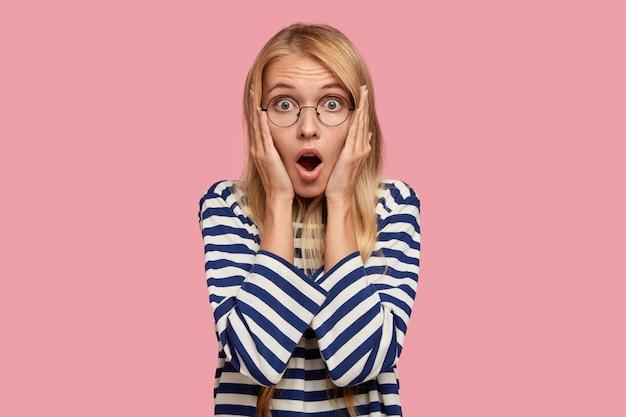 Фото ошеломленной красивой блондинки, уставившейся на камеру с приглушенными глазами, широко открыв рот