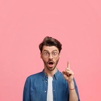어두운 수염을 가진 stupefied 백인 남성의 사진은 입을 넓게 열어두고 유행의 옷을 입고 앞쪽 손가락으로 위쪽을 가리키며 분홍색 벽에 위쪽으로 빈 공간을 나타냅니다.
