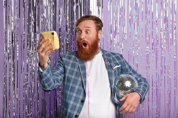 赤い髪とあごひげを生やした愚かな白人男性の写真、腕の下にディスコボールを持って、驚くほどに見え、自分の写真を作り、スタイリッシュな服を着て、オフィスパーティーで楽しんでいます