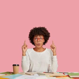 어리둥절한 곱슬 여성 디자이너의 사진은 흰색 스웨터와 안경을 착용하고 천장에 두 검지 손가락으로 포인트를 주며 복사 공간을 보여주고 데스크톱에서만 포즈를 취하고 창의적인 프로젝트를 준비합니다.