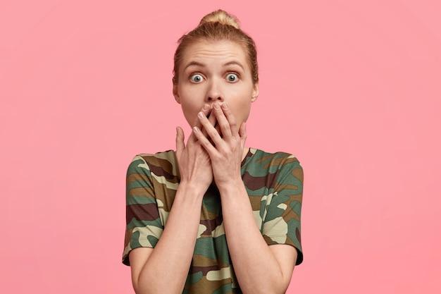 愚かな感情的な若いヨーロッパの女性の写真は、結び目でとかされた明るい髪を持ち、両手で口を覆い、驚きで叫び、ピンクの壁にポーズをとり、カジュアルなtシャツを着ています