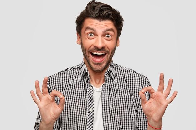 На фото стильный бородатый молодой мужчина с модной стрижкой, хорошо жестикулирует обеими руками, одет в клетчатую рубашку, смотрит глазами, изолированный на белой стене. концепция языка тела