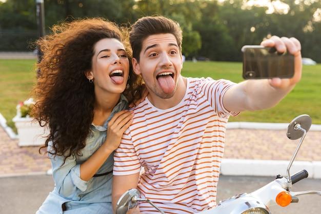 도시 공원에서 오토바이에 함께 앉아있는 동안 휴대 전화에 셀카를 복용 세련된 커플의 사진