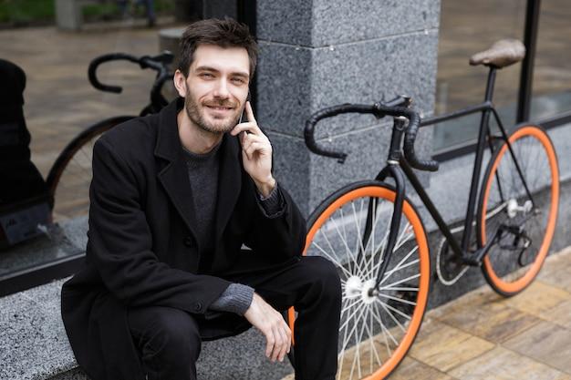 자전거와 함께 야외에 앉아있는 동안 휴대 전화를 사용하는 세련된 남자 20 대의 사진