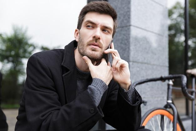자전거와 함께 야외에 앉아있는 동안 스마트 폰을 사용하는 세련된 남자 20 대의 사진