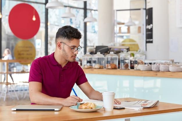 トレンディなヘアカットをしたスタイリッシュな男性の写真、メモ帳にレコードを書き込み、新聞に焦点を当て、持ち帰り用のコーヒーを飲み、フリーランスの仕事に最新のラップトップコンピューターを使用しています。流行に敏感な男が録音をする