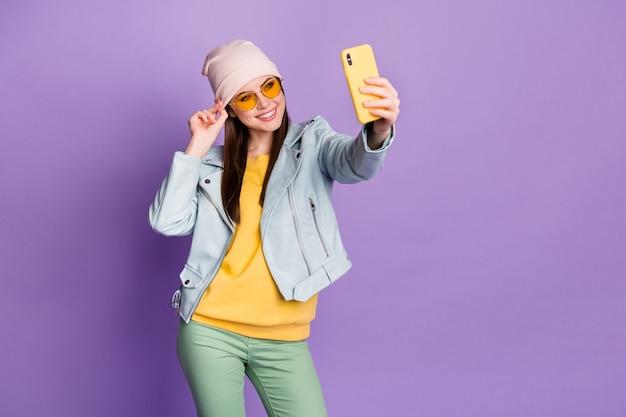 スタイリッシュでかなり素敵な女性の写真は電話を笑顔で保持しますselfiesフォロワーを作る人気のブロガーは太陽のスペックを着用しますカジュアルな帽子青いジャケットプルオーバー緑のズボン孤立した紫色の背景