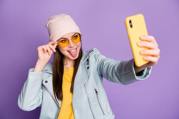 세련된 예쁜 젊은 여성이 전화를 들고 웃는 혀를 내밀고 있는 사진은 셀카 추종자 블로거가 태양 사양 캐주얼 모자 재킷 노란색 풀오버 격리된 보라색 배경을 착용하게 합니다.