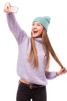 Фотография стильной симпатичной молодой женщины, держащей телефон, улыбающейся торчащей языком, заставляющей последователей селфи носить солнцезащитные очки, повседневная шляпа, куртка, желтый пуловер, изолированная белая стена