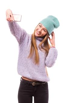 세련 된 예쁜 젊은 여자의 사진 보류 전화 미소 고집 혀 만들기 셀카 추종자 블로거 착용 태양 사양 캐주얼 모자 재킷 노란색 풀오버 절연 흰색 벽