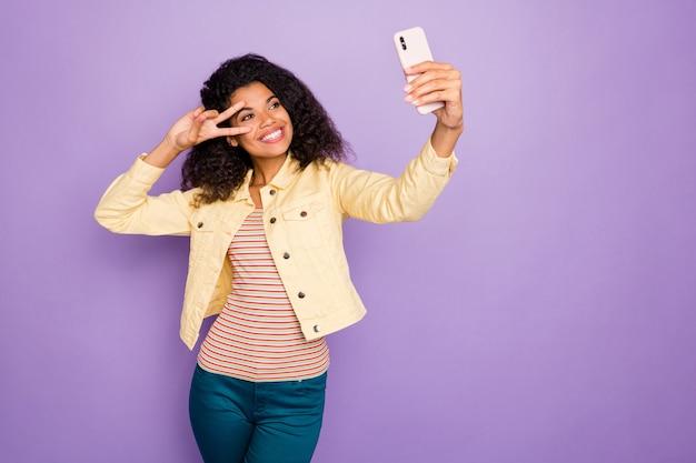 Фото стильной модной веселой позитивной симпатичной симпатичной девушки, показывающей vsign в полосатой футболке, брюках, брюках, улыбке, зубастой, изолированной, пастельно-фиолетовом цветном фоне