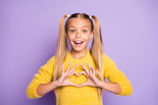 Фото стильной модной веселой позитивной девушки, показывающей знак в форме сердца с эмоциями на лице, изолированной в желтом свитере на стене пастельного фиолетового цвета