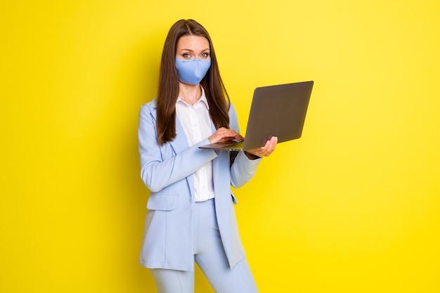 호흡기 마스크를 쓴 성공 회사 사장 여성의 사진 원격 사용 노트북 타이핑 이메일은 밝은 색 배경 위에 격리된 파란색 재킷 블레이저 바지 바지를 입고 있습니다.