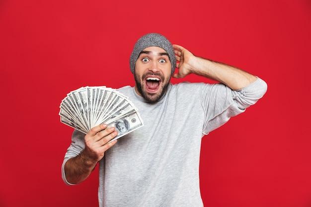 Фотография успешного парня 30-х годов в повседневной одежде, радующегося и держащего в руках наличные деньги