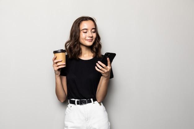 회색 벽 위에 절연 손에 스마트 폰과 테이크 아웃 커피와 함께 서있는 공식적인 마모에 성공적인 여자의 사진