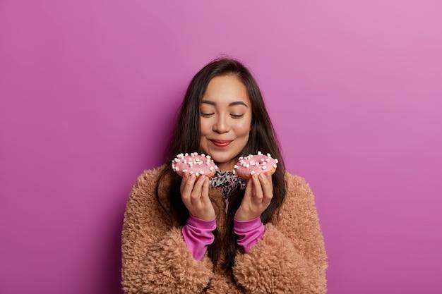 설탕에 중독 된 여성의 사진은 갓 구운 도넛 냄새, 디저트 먹기에 저항 할 수 없음, 좋은 식욕으로 디저트를 먹을 준비가되었습니다.