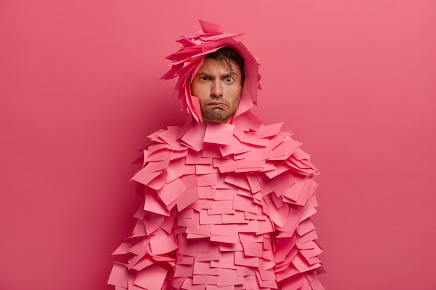 不機嫌そうなヨーロッパ人男性の写真は眉を上げ、暗い表情をし、不幸なしかめっ面をし、バラ色のステッカーを身に着け、何かに不満を抱き、ピンクの壁に隔離されています