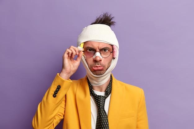 目の近くに打撲傷、血腫、脳震盪を起こした不機嫌そうな男性の写真。包帯、フォーマルなスーツとネクタイを着用し、残酷な人々に殴られ、紫色の壁に隔離されています。健康問題の概念
