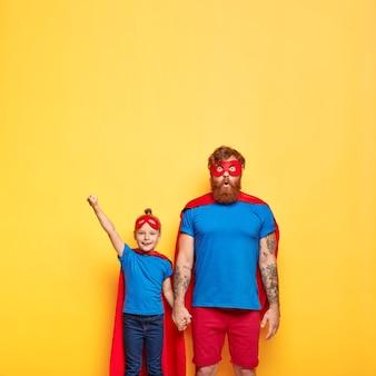놀란 아버지의 사진은 비행 제스처를 만드는 작은 딸의 손을 잡고