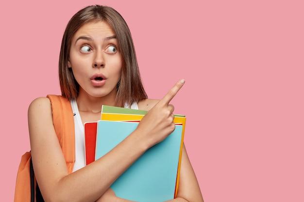 Фотография удивленной, удивленной темноволосой женщины смотрит с удивлением в сторону, указывает на место для копирования
