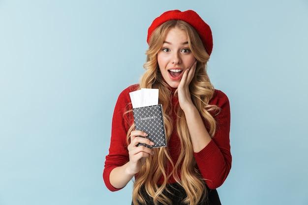 Фотография удивленной белокурой девушки 20-х годов в красном берете с изолированным паспортом и проездным билетом
