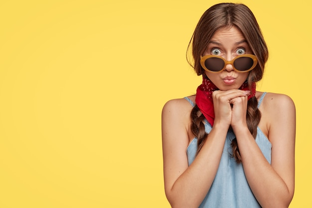 驚いたブルネットの女性の写真は唇を丸め、面白い表情を作り、サングラスを通して見つめます