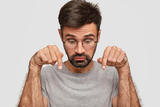 Фотография удивленного мужчины европеоидной расы с заторможенными глазами, щетиной, указывает вниз, потрясенно смотрит, небрежно одетый, изолированный на белой стене люди, удивление и недоверие.