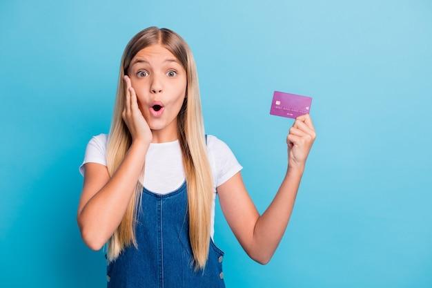 Фотография удивленной веселой светловолосой девушки-подростка с банковской картой в повседневной одежде, изолированной на пастельно-синем цветном фоне