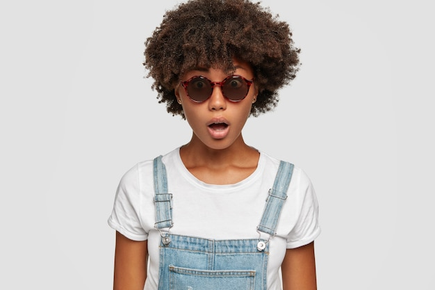 アフロの髪型で驚いた浅黒い肌の女性の写真、口を開けたまま、突然のフェイクニュースに反応