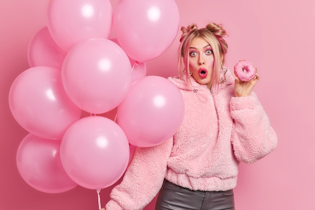 Фотография удивленной европейской женщины с прической в модной одежде, держащей восхитительный пончик и воздушных шаров на вечеринке по случаю дня рождения, потрясенная получением неожиданного подарка моделям в помещении. все в розовом