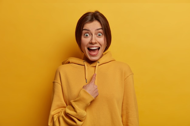 놀란 흥분된 쾌활한 젊은 여성의 사진은 자신을 나타내며 리더로 선택되는 것을 믿지 않으며 노란색 벽 위에 고립 된 캐주얼 셔츠를 입습니다. 선택적 초점. 누구, 나?