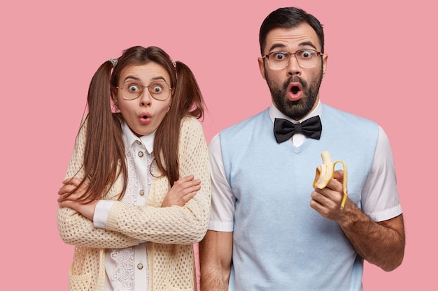 驚いた女性と男性のウインクの写真は、不信感を持って見つめ、古いファッショナブルな服を着て、おいしいバナナを食べます