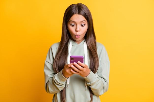 驚いた面白い女子高生の写真は、手をつないで探しているカジュアルな灰色の服を着ています腕現代のガジェット分離された黄色の背景