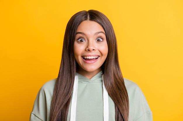 Фотография удивленной смешной школьницы в повседневной серой одежде, улыбаясь большими глазами, изолировала желтый цвет фона
