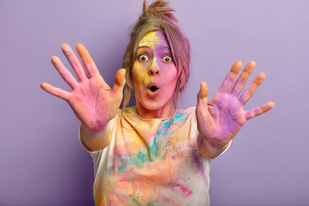 色付きの顔、手のひら、服を着て驚いた面白い女性の写真、ホリ祭を祝う、色で遊ぶ、手を伸ばす、紫色の壁に隔離された粉末染料を使用