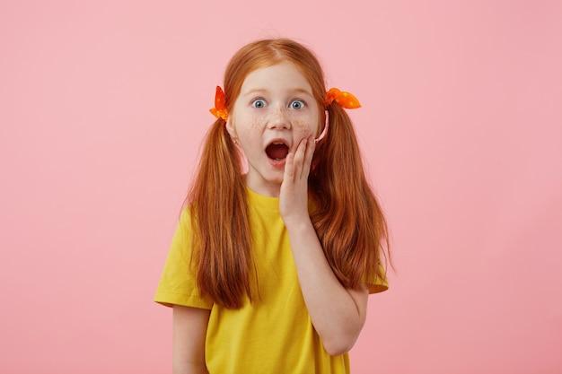 Фотография удивленной веснушчатой рыжеволосой девочки с двумя хвостами, смотрит в камеру с широко открытым ртом и глазами, трогает щеку, носит желтую футболку, стоит на розовом фоне.