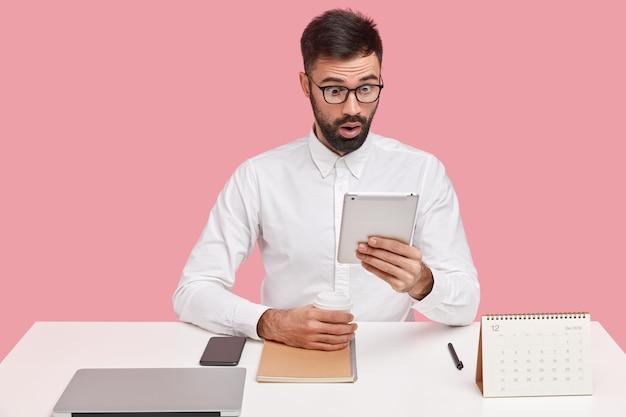 驚いた男性従業員の写真は、タッチパッドの画面を見つめ、驚きを感じ、衝撃的なメッセージを読み、使い捨てカップからコーヒーを飲み、眼鏡をかけています。