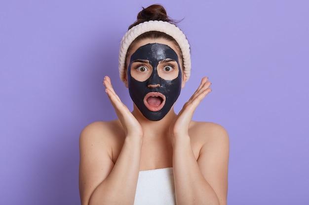 열린 입으로 놀란 말이없는 여자의 사진은 진흙 얼굴 마스크를 착용하고, 미용 절차, 충격을받은 표정으로 소녀, 몸에 수건을 감싸고, 라일락 벽에 고립되어 손바닥을 얼굴 근처에 유지합니다.