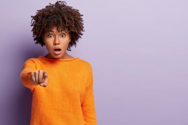 На фото удивленная, испуганная кудрявая женщина показывает прямо указательным пальцем, открывает рот от шока, демонстрирует что-то впереди, носит повседневную одежду, модели поверх фиолетовой стены
