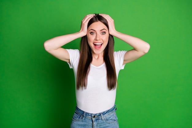 놀란 학생의 사진은 캐주얼 복장을 하고 머리를 벌리고 고립된 녹색 배경입니다.