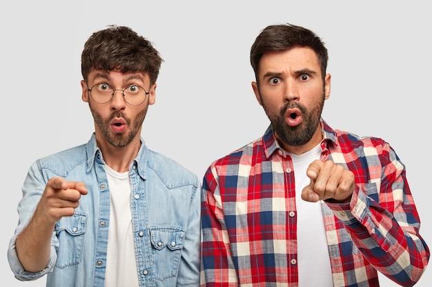 Фотография удивленных двух мужчин с удивленным выражением лица, указывающих прямо указательными пальцами, выражающих шок, стоящих рядом друг с другом, указывающих вдаль, изолированных на белой стене