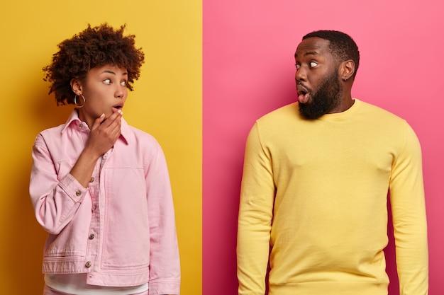 驚いた女性と男性がお互いにショックで見て、悪いニュースを聞いて恥ずかしい思いをし、彼らの目を信じることができず、カジュアルな服を着て、ピンクと黄色の壁に隔離された写真