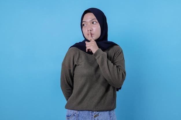 ヒジャーブを身に着けている驚いた女性の写真は秘密を守り、沈黙を求め、人差し指を唇に押し付け、静けさの兆候を示しています