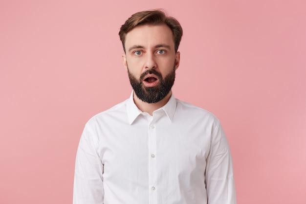 白いシャツを着て秘密を告げられた驚いた若いハンサムなあごひげを生やした男の写真。ピンクの背景の上に分離された大きく開いた口でカメラを見てください。