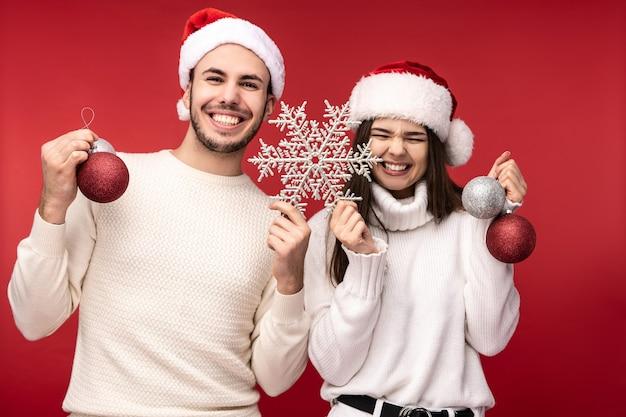 Фотография сладкой парочки в новогодних шапках и с новогодними игрушками, радующихся праздникам. мужчина и женщина влюблены, выглядят благословенными и улыбаются, изолированные на красном фоне.