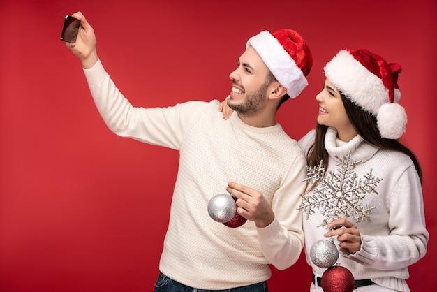 Фотография сладкой парочки в новогодних шапках и с елочными игрушками выглядит счастливой. мужчина и женщина делают селфи и улыбаются, изолированные на красном фоне.